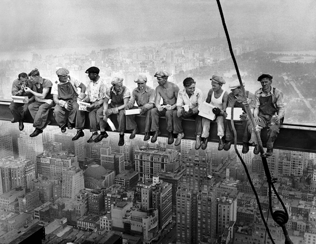 Construction workers eat lunch 200 feet up in the air.