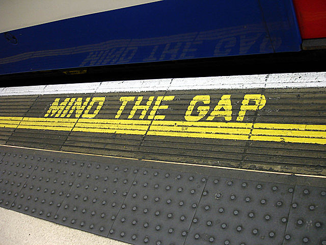 Mind the Gap sign on platform in front of tube train