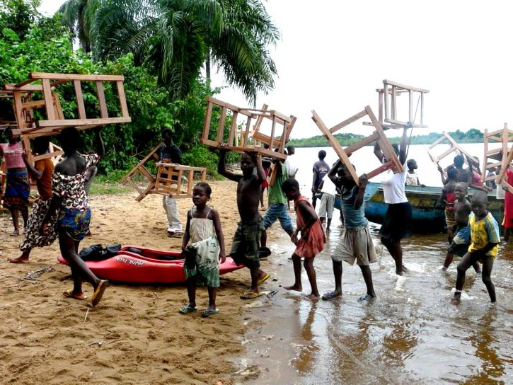 collaboration in practice as teachers and pupils unload school furniture from a boat