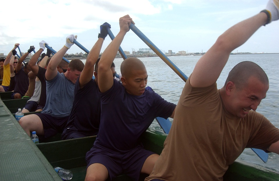 a rowing team with oars on the same side of the boat
